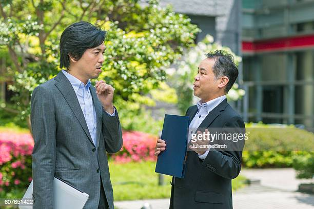 Japanese businessmen discussing work in a garden
