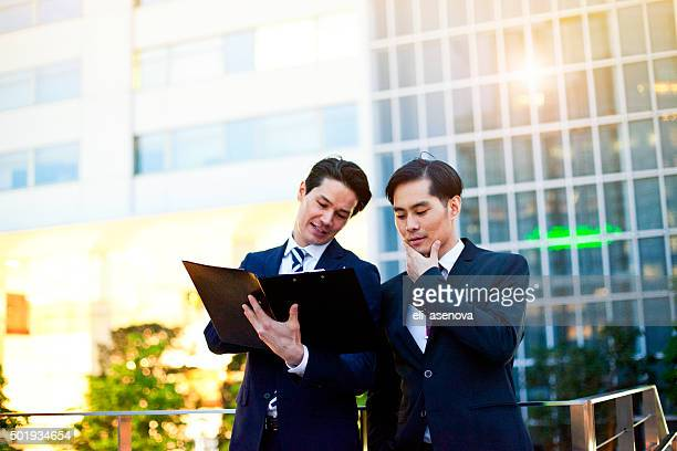 Japanese businessmen in Tokyo having the working conversation outdoors