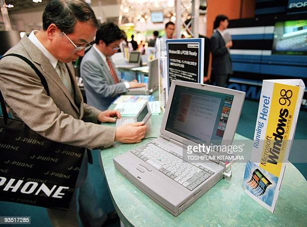 Japanese businessmen try Microsoft's new operating sytem Windows 98 Japanese version at the Toshiba booth 19 May at Tokyo's Business Show 98 Softwear...