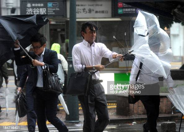 Japanese businessmen walk against strong wind and rain in Tokyo on October 16 2013 At least three people died as Typhoon Wipha the 'strongest in 10...