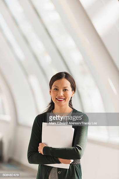 Japanese businesswoman carrying papers in lobby