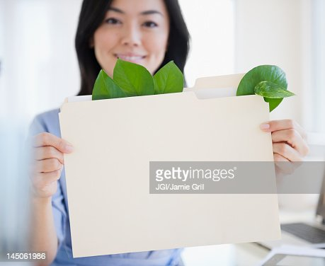 Japanese businesswoman holding folder containing leaves : Stock Photo