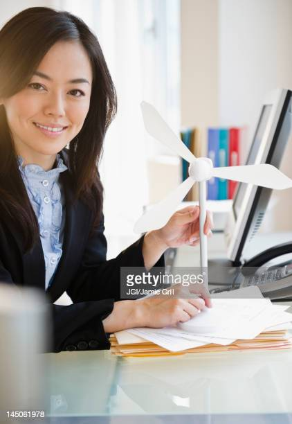 Japanese businesswoman holding model wind turbine