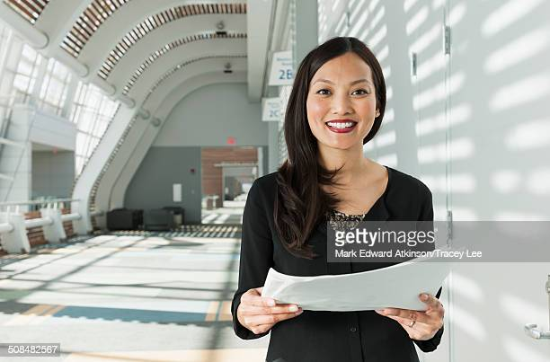 Japanese businesswoman holding papers in office