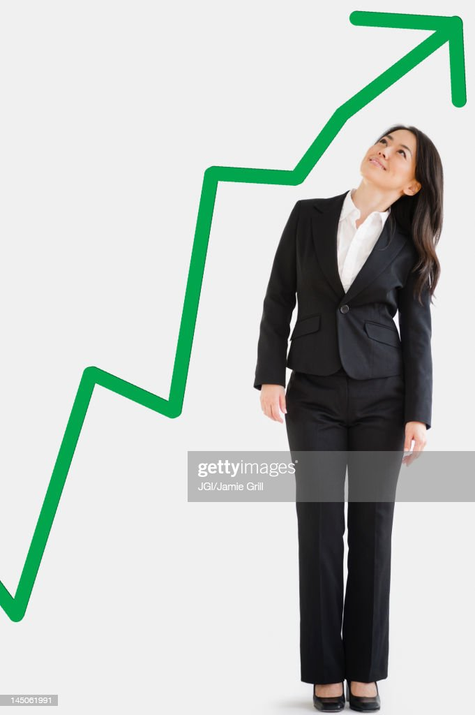 Japanese businesswoman looking at green arrow