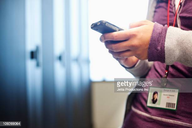 Japanese businesswoman using cell phone in office technology room