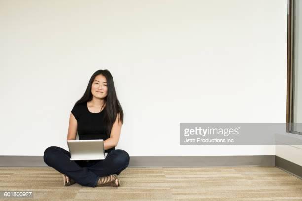 Japanese businesswoman using digital tablet in empty office
