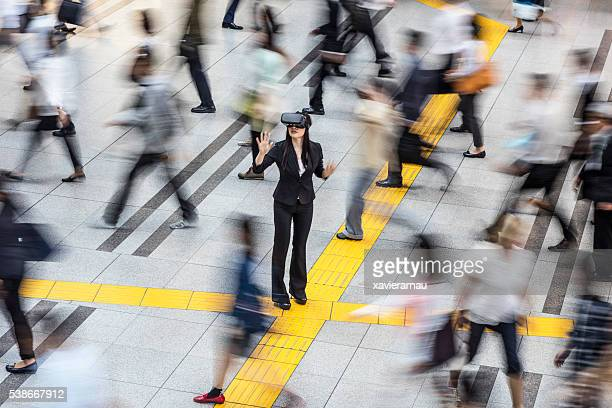 Japanese businesswoman using the VR simulator in the street