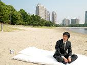 Japanese bussiness man sitting on futon, at beach