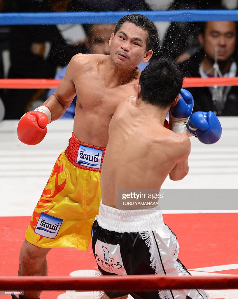 Japanese challenger Kohei Kono (R-back to camera) and champion Tepparith Kokietgim (L) of Thailand exchange blows in the fourth round of their WBA super flyweight title boxing bout in Tokyo on December 31, 2012. The 32-year-old Japanese sent Tepparith onto the ring floor three times in the fourth round to finish off the Thai boxer two minutes, eight seconds into the stanza. AFP PHOTO / Toru YAMANAKA