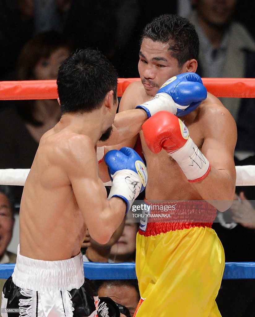 Japanese challenger Kohei Kono (L-back to camera) and champion Tepparith Kokietgim (R) of Thailand exchange blows in the fourth round of their WBA super flyweight title boxing bout in Tokyo on December 31, 2012. The 32-year-old Japanese sent Tepparith onto the ring floor three times in the fourth round to finish off the Thai boxer two minutes, eight seconds into the stanza. AFP PHOTO / Toru YAMANAKA