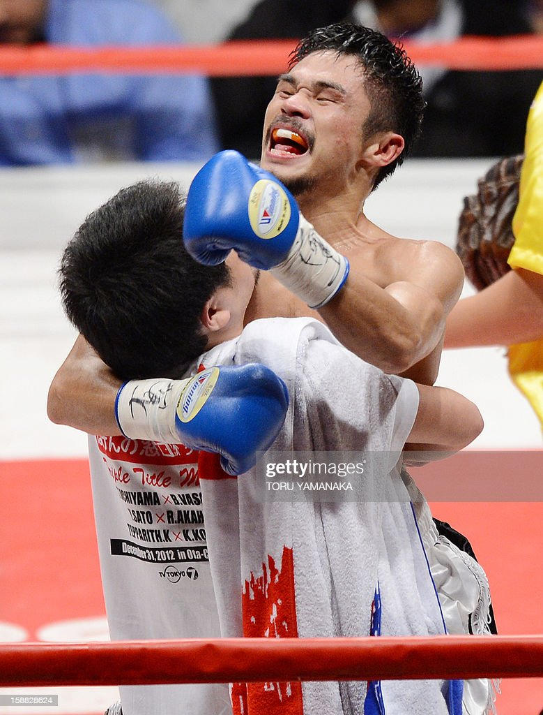Japanese challenger Kohei Kono (R) celebrates with his corner after knocking out champion Tepparith Kokietgim of Thailand in the fourth round of their WBA super flyweight title boxing bout in Tokyo on December 31, 2012. The 32-year-old Japanese sent Tepparith onto the ring floor three times in the fourth round to finish off the Thai boxer two minutes, eight seconds into the stanza. AFP PHOTO / Toru YAMANAKA