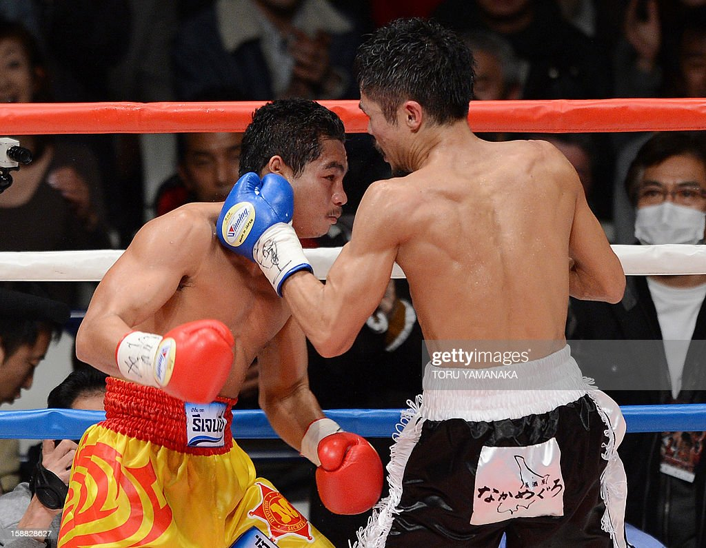 Japanese challenger Kohei Kono (R) connects with a left against champion Tepparith Kokietgim (L) of Thailand in the fourth round of their WBA super flyweight title boxing bout in Tokyo on December 31, 2012. The 32-year-old Japanese sent Tepparith onto the ring floor three times in the fourth round to finish off the Thai boxer two minutes, eight seconds into the stanza. AFP PHOTO / Toru YAMANAKA