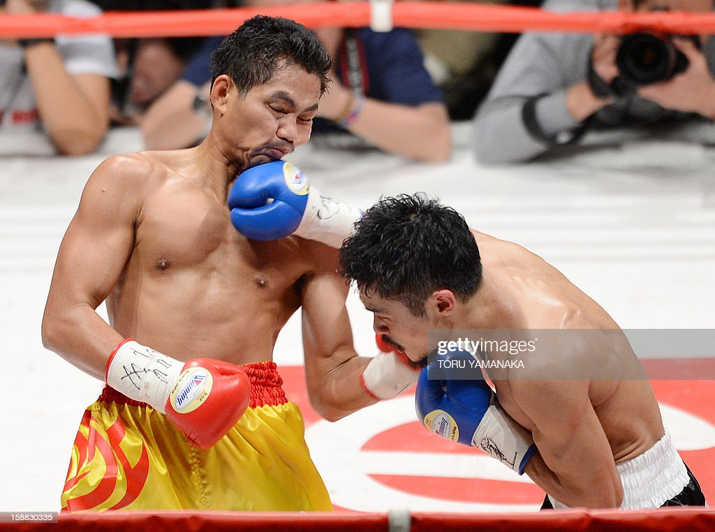 Japanese challenger Kohei Kono (R) connects with a right to champion Tepparith Kokietgim (L) of Thailand in the second round of their WBA super flyweight title boxing bout in Tokyo on December 31, 2012. The 32-year-old Japanese sent Tepparith onto the ring floor three times in the fourth round to finish off the Thai boxer two minutes, eight seconds into the stanza. AFP PHOTO / Toru YAMANAKA