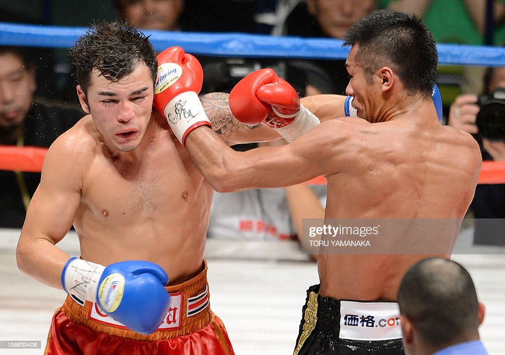 Japanese champion Takashi Uchiyama (R) and Bryan Vasquez (L) of Costa Rica exchange blows during the seventh round of the WBA super featherweight title bout in Tokyo on December 31, 2012. Uchiyama defeated Vasquez with a technical knockout to defend the title. AFP PHOTO/ Toru YAMANAKA