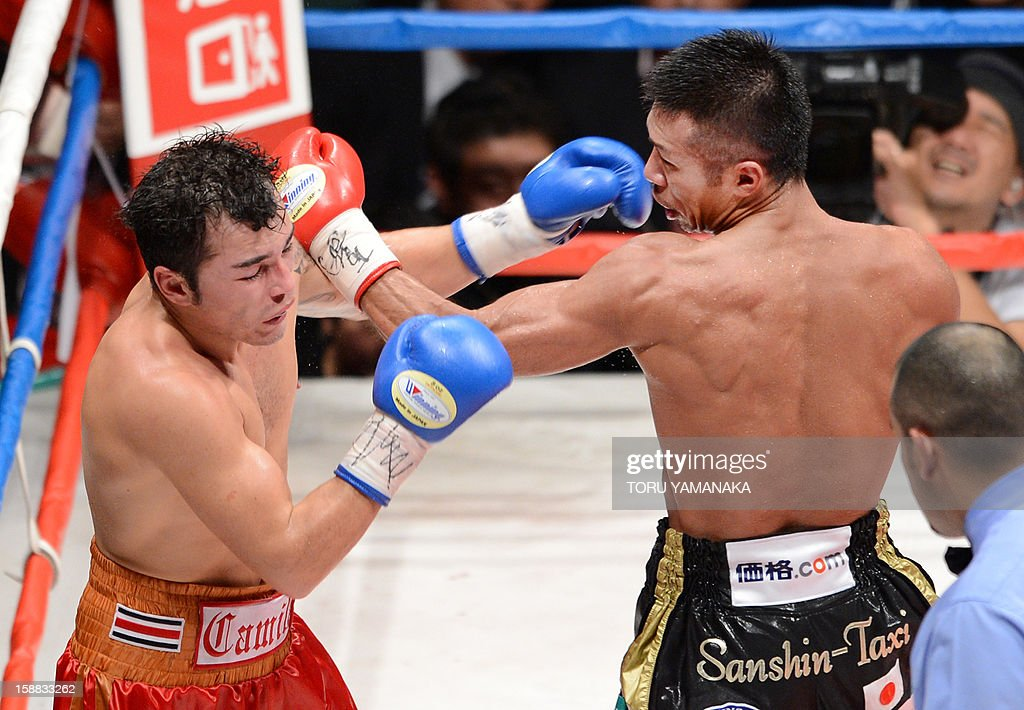 Japanese champion Takashi Uchiyama (R) fights against Bryan Vasquez of Costa Rica (L) in the eighth round of their WBA super featherweight title bout in Tokyo on December 31, 2012. Uchiyama defeated Vasquez with a technical knockout to defend the title. AFP PHOTO / Toru YAMANAKA