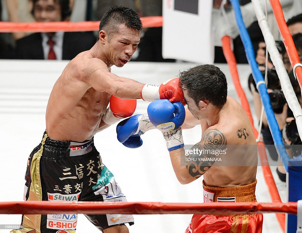 Japanese champion Takashi Uchiyama (L) fights against Bryan Vasquez of Costa Rica in the eighth round of their WBA super featherweight title bout in Tokyo on December 31, 2012. Uchiyama defeated Vasquez with a technical knockout to defend the title. AFP PHOTO / Toru YAMANAKA