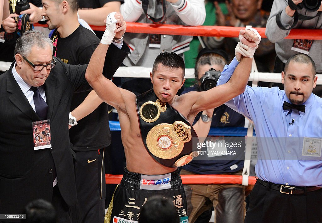 Japanese champion Takashi Uchiyama (C) raises his arms after his victory over Bryan Vasquez of Costa Rica in their WBA super featherweight title bout in Tokyo on December 31, 2012. Uchiyama defeated Vasquez with a technical knockout to defend the title. AFP PHOTO / Toru YAMANAKA