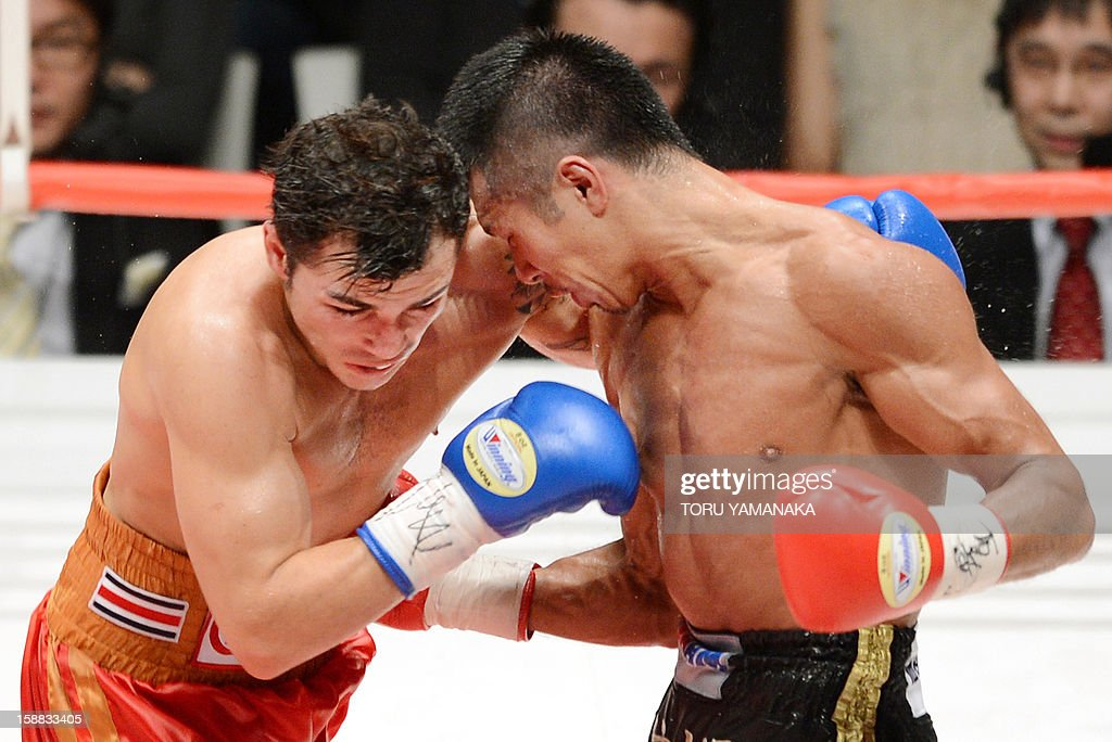 Japanese champion Takashi Uchiyama (R) sends a right blow to Bryan Vasquez (L) of Costa Rica during the seventh round of the WBA super featherweight title bout in Tokyo on December 31, 2012. Uchiyama defeated Vasquez with a technical knockout to defend the title. AFP PHOTO/ Toru YAMANAKA