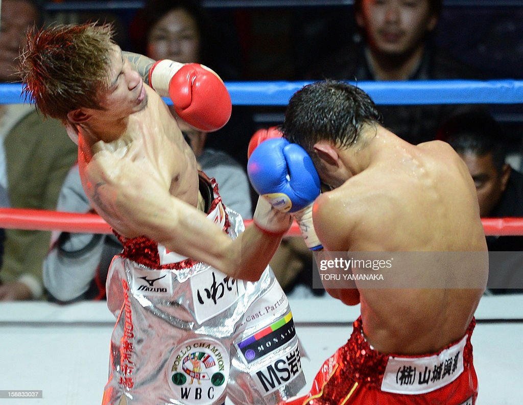 Japanese champion Yota Sato (L) connects with a right to challenger Ryo Akaho (R) of Japan in the 12th round of their WBC super flyweight title bout in Tokyo on December 31, 2012. Sato defeated Akaho with a decision to defend the title. AFP PHOTO/Toru YAMANAKA