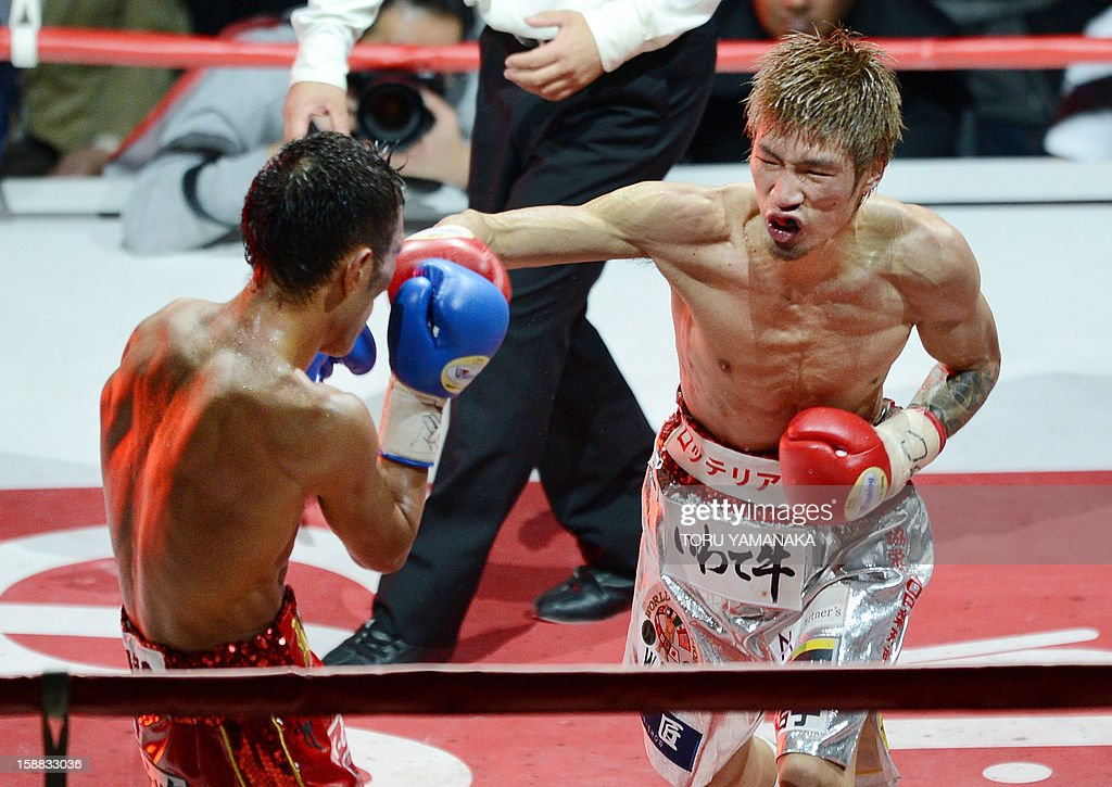 Japanese champion Yota Sato (R) sends a right to challenger Ryo Akaho (L) of Japan in the 12th round of their WBC super flyweight title bout in Tokyo on December 31, 2012. Sato defeated Akaho with a decision to defend the title. AFP PHOTO/Toru YAMANAKA