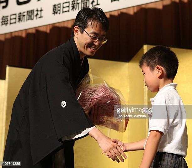 Japanese chess player Yoshiharu Habu shakes hands with his fan after receiving a flower bunch during the 67th 'Miejin' title awarding ceremony at...
