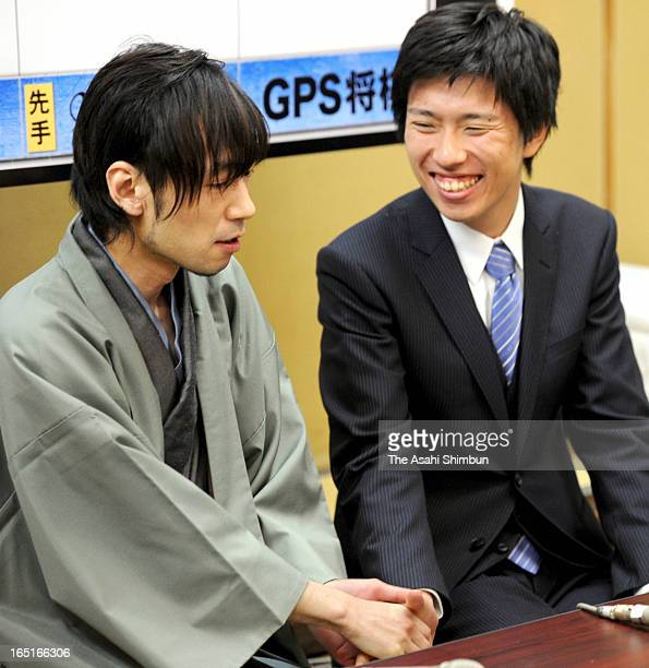 Japanese chess 'shogi' master Shinichi Sato Issei Yamamoto who has developed the shogi program 'Ponanza' shake hands after the computer program first...