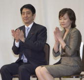 Japanese Chief Cabinet Secretary Shinzo Abe and his wife Akie Abe applaud during a press conference to announce his intention to stand as Prime...