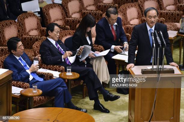 Japanese Chief Cabinet Secretary Yoshihide Suga answers questions while Prime Minister Shinzo Abe looks on during a budget committee session of the...