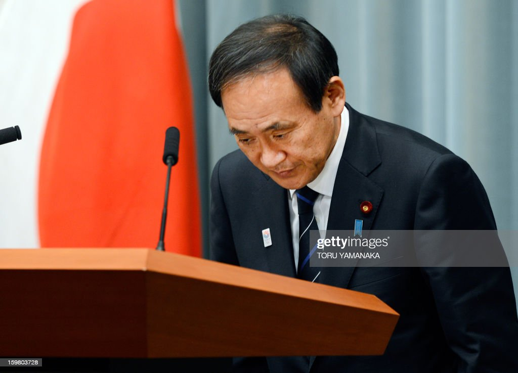 Japanese Chief Cabinet Secretary Yoshihide Suga bows to the press before a press conference to explain the hostage crisis in Algeria, at the prime minister's official residence in Tokyo on January 21, 2013. Twelve bodies being held at a morgue in Algeria's In Amenas hospital, where victims of a bloody hostage crisis were taken, are Japanese, a hospital source said on January 20. AFP PHOTO/Toru YAMANAKA