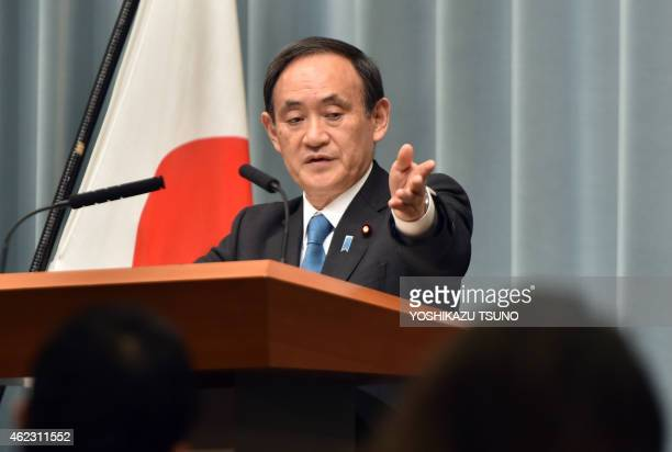 Japanese Chief Cabinet Secretary Yoshihide Suga speaks to reporters after a cabinet meeting at prime minister's official residence in Tokyo on...