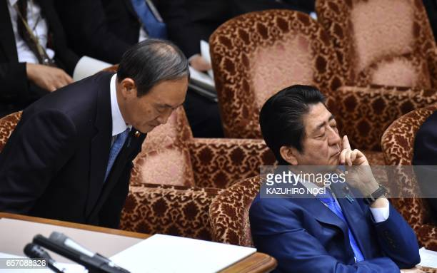 Japanese Chief Cabinet Secretary Yoshihide Suga walks beside Prime Minister Shinzo Abe during a budget committee session of the House of Councilors...