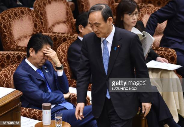 Japanese Chief Cabinet Secretary Yoshihide Suga walks past Prime Minister Shinzo Abe after answering questions during a budget committee session of...