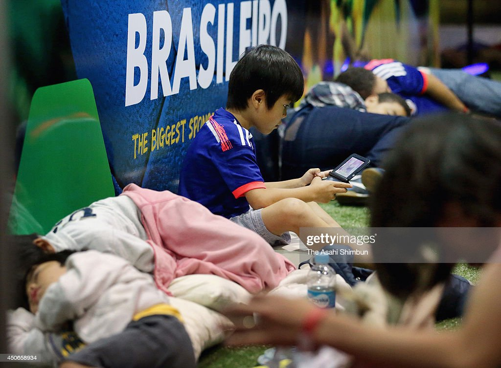 A Japanese child plays with a portable game console while Japanese supporters wait for the airplane early in the morning at Recife Airport on June 15, 2014 in Recife, Brazil.