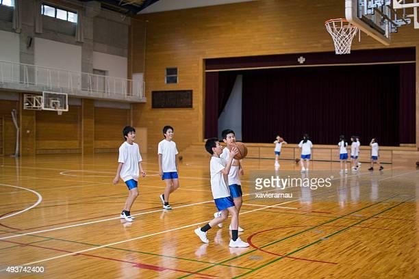 日本の子供の practising バスケットボール体育館