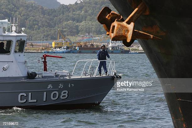 Japanese Coast Guard boat stands watch as North Korean ship loads a cargo of used bicycles and refrigerators at the Maizuru port October 13 2006 in...