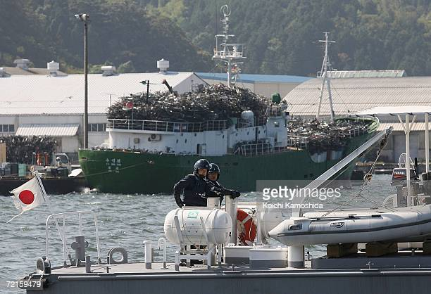 Japanese Coast Guard boat stands watch as North Korean ship packs a cargo of used bicycles and refrigerators at the Maizuru port October 13 2006 in...