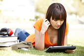 Japanese college student studying on tablet in grass