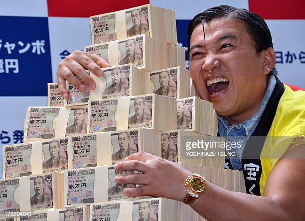 Japanese comedian Sugichan poses with 500 million yen for the Summer Jumbo Lottery as the the first tickets went on sale in Tokyo on July 10 2013...