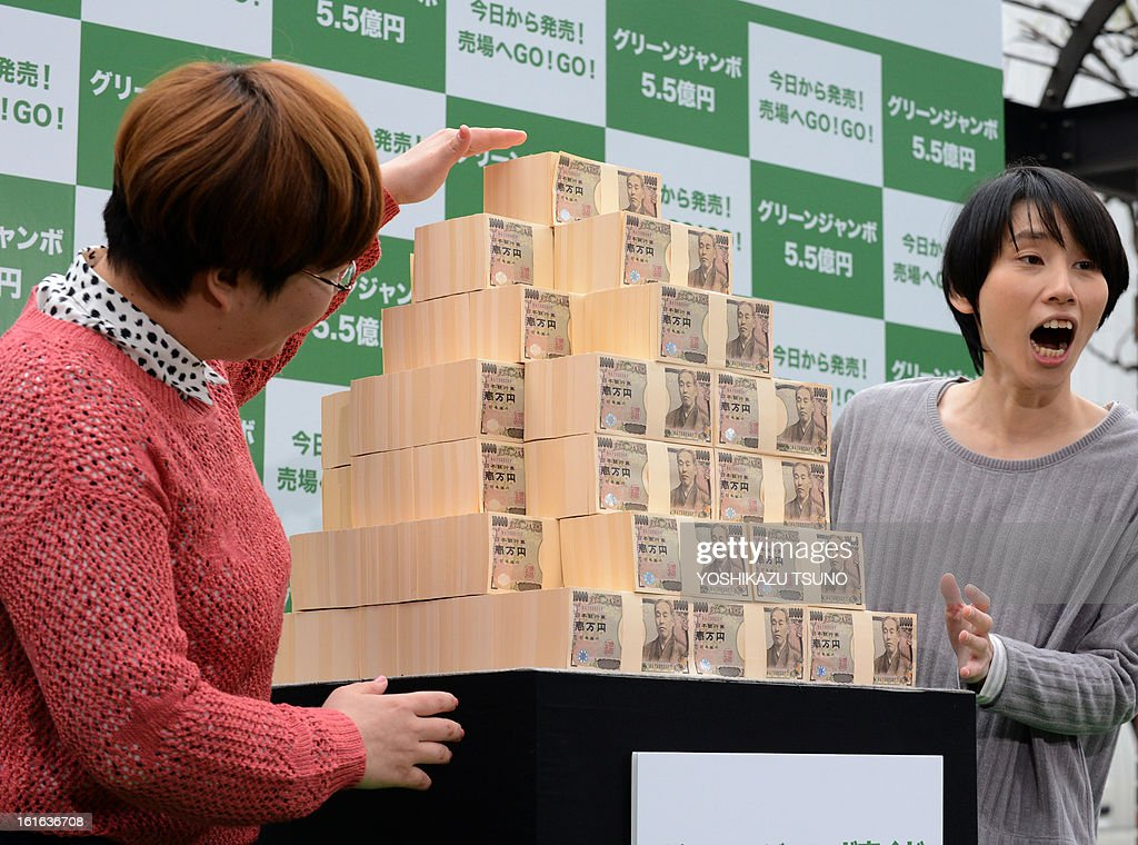 Japanese comedians Haruka Minowa (R) and Haruna Kondo display 550 million yen (6 million USD) for the Green Jumbo Lottery as the the first tickets went on sale in Tokyo on February 14, 2013. Thousands of punters queued up for tickets in the hope of becoming a millionaire. AFP PHOTO / Yoshikazu TSUNO