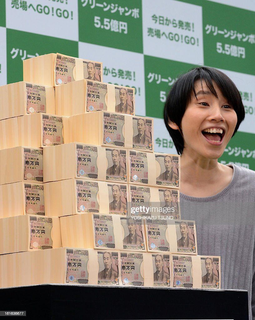 Japanese comedians Haruka Minowa displays 550 million yen (6 million USD) for the Green Jumbo Lottery as the the first tickets went on sale in Tokyo on February 14, 2013. Thousands of punters queued up for tickets in the hope of becoming a millionaire. AFP PHOTO / Yoshikazu TSUNO