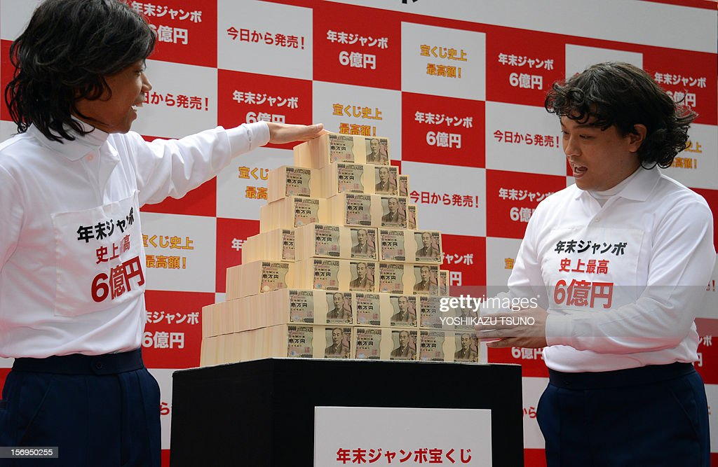 Japanese comedians Kenji Tada (L) and Yoshi Yamada pose with 600 million yen (7.3 million USD) for the year-end Jumbo Lottery as the the first tickets went on sale in Tokyo on November 26, 2012. Thousands of punters queued up for tickets in the hope of becoming a millionaire. AFP PHOTO / Yoshikazu TSUNO