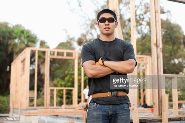 Japanese construction worker in sunglasses with arms crossed
