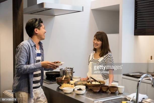 Japanese couple at home in kitchen, talking