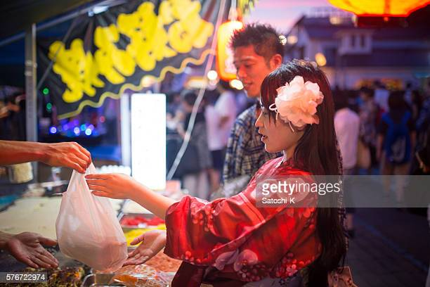 Japanese couple buying okonomiyaki at festival