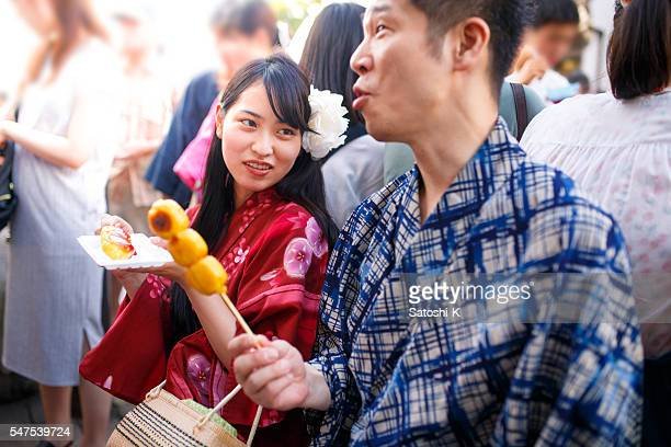 Japanese couple eating Dango rice dumpling at festival