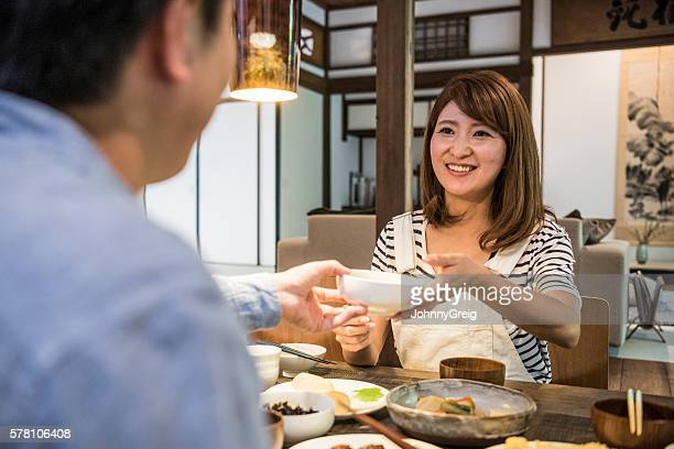 Japanese couple having dinner, woman passing bowl to man