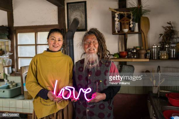 Japanese couple in their rural kitchen with a neon love sign