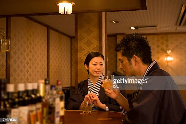 Japanese couple in Yukata drinking at the hotel bar, front view, side view, Japan