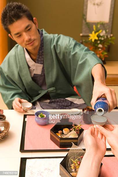 Japanese couple in Yukata having dinner, man pouring Sake, front view, Japan